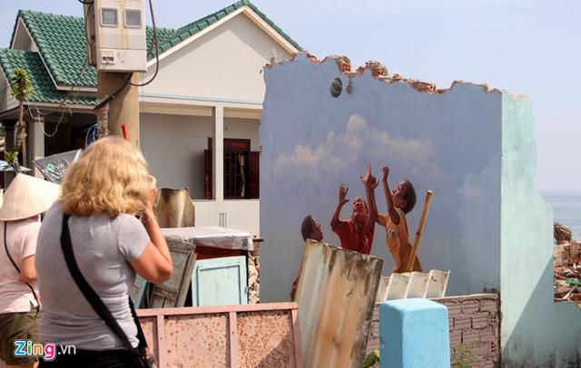 Nhiều du khách tỏ vẻ luyến tiếc khi biết những bức tranh sẽ bị đập bỏ nên họ tranh thủ lưu lại hình ảnh để làm kỷ niệm. Ảnh: Đắc Đức.