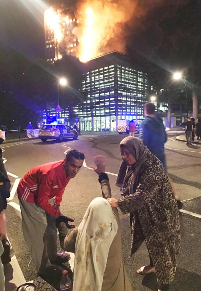 Hình ảnh người còn sống mắc kẹt bên trong tòa nhà 27 tầng bị lửa bao trùm, nhiều người được xác nhận đã chết - Ảnh 9.